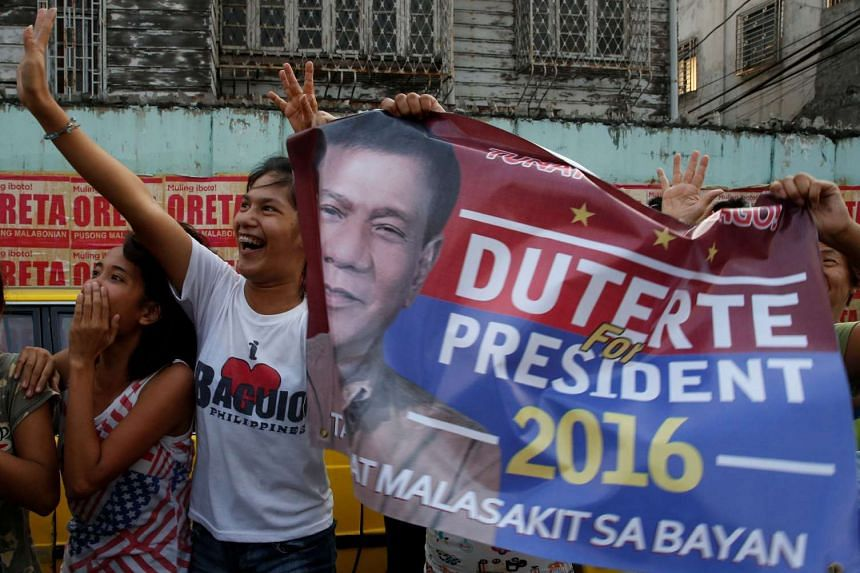 """Supporters chant slogans as the motorcade of presidential candidate Rodrigo """"Digong"""" Duterte passes by during election campaigning in Malabon on April 27, 2016."""