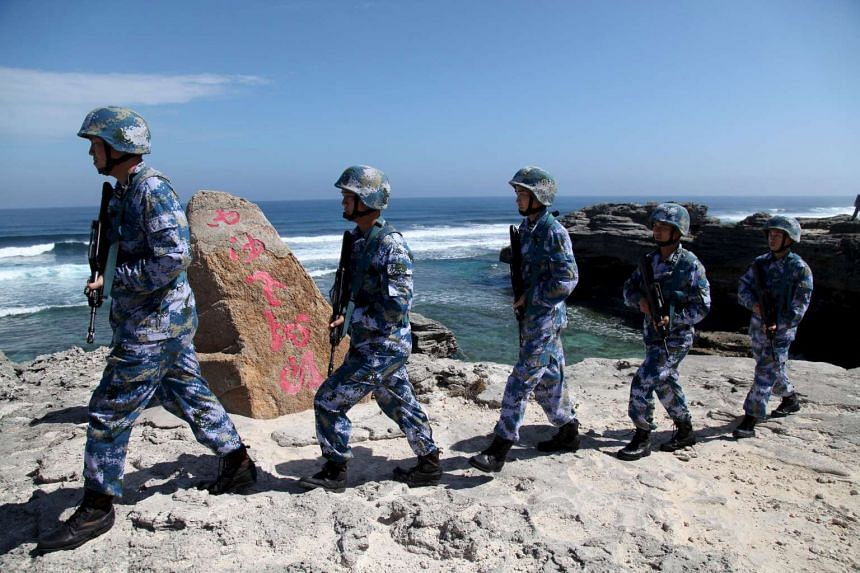 Soldiers of China's People's Liberation Army Navy (PLAN) patrol at Woody Island, in the Paracel Archipelago, on Jan 29, 2016.