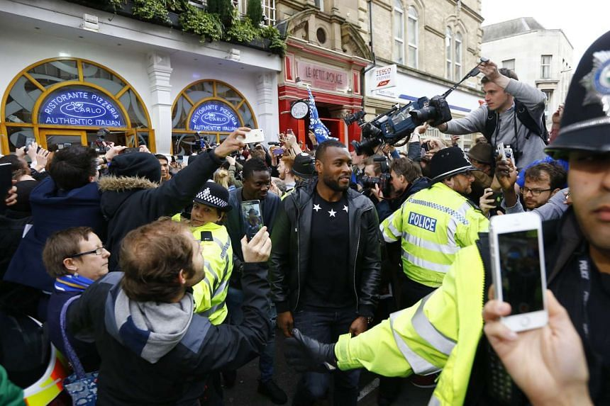 Leicester City captain Wes Morgan (middle) mobbed by fans after a celebratory team lunch on May 3, 2016, the day after the Foxes won the English Premier League title.