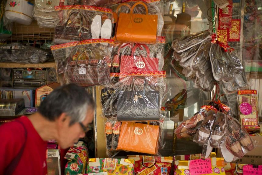 A man walking past a store selling paper replicas of items used as offerings for deceased relatives and displaying paper luxury bags in Hong Kong.