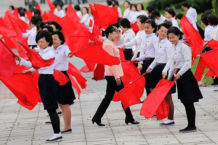 Girls on Wednesday practising dancing with red flags in central Pyongyang ahead of today's party congress. The event marks the political high point of Mr Kim's four-year rule.