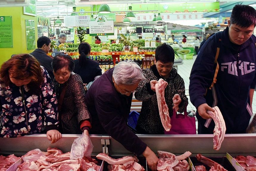 Customers shopping for pork at a supermarket in Hangzhou, Zhejiang province, on April 11.