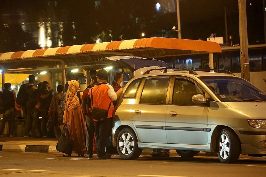 Passengers entering a car offered by a tout near the intersection next to the Ban San Street terminal last Friday. These illegal cross-border taxis charge fees which can range from $10 to $30 per person. A check found at least 20 making use of apps l