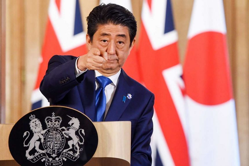 Abe gestures during a joint news conference with British Prime Minister David Cameron.