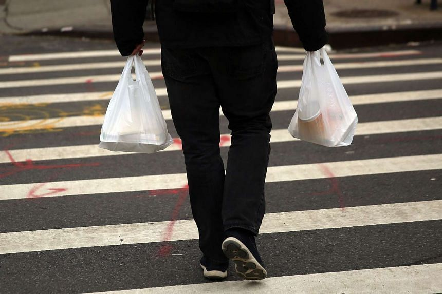 A man walks out of a store with a plastic bags in New York City, on May 5, 2016.