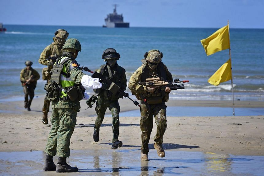 Troops from the Singapore Armed Forces and the Seventh Australian Regiment of the Australian Defence Force take part in a military exercise on a beach in Rockhampton, Queensland, on Nov 8, 2014.