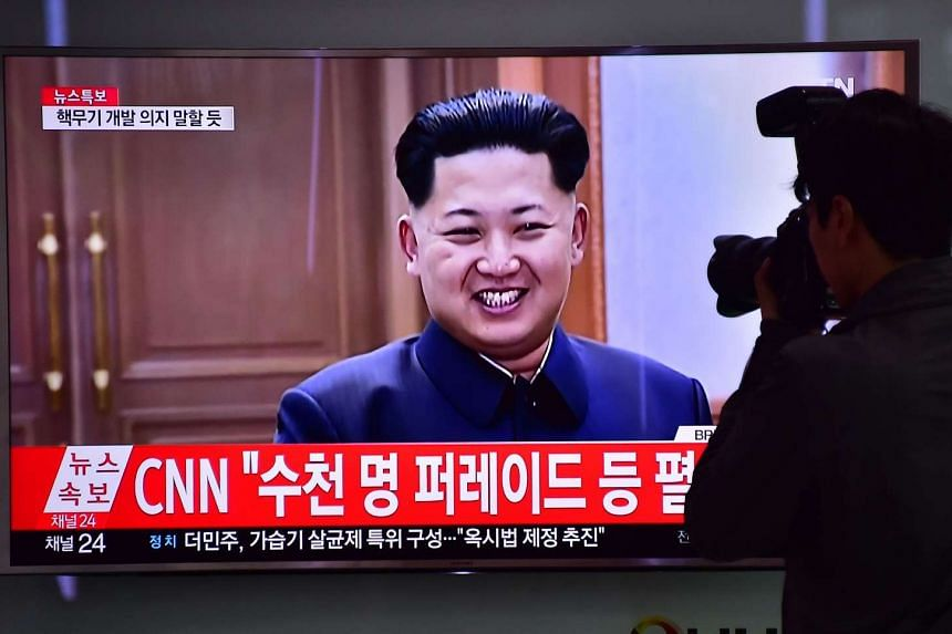 A photographer takes a picture of a TV screen showing file footage of North Korean leader Kim Jong-Un in Seoul, on May 6, 2016.