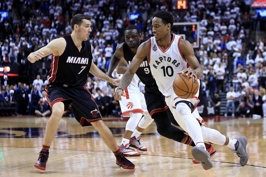 DeMar DeRozan #10 of the Toronto Raptors dribbles the ball as Goran Dragic #7 and Luol Deng #9 of the Miami Heat defend at the 2016 NBA Playoffs.