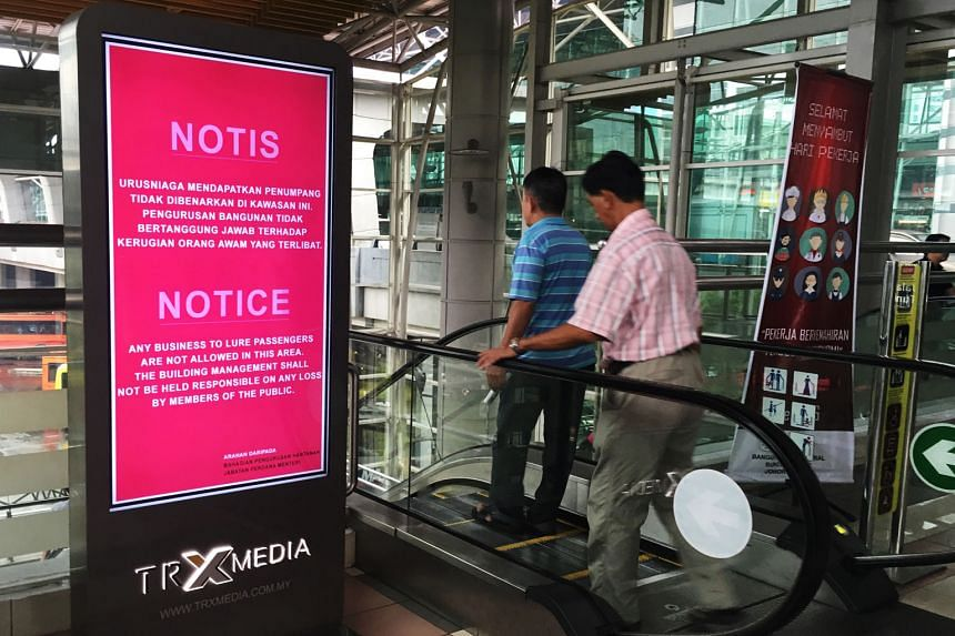 Touts remain active despite signs put up by the authorities warning against them, like these at JB Sentral train station seen last month.