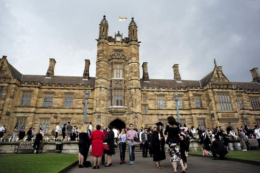 University students walk on the campus of University of Sydney following a graduation ceremony in Sydney, Australia.
