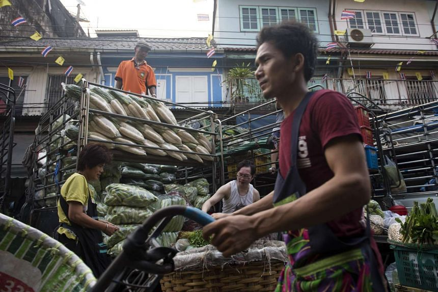 People sell fruits and vegetables in Pak Klong Talad Market in Bangkok on March 22, 2016.