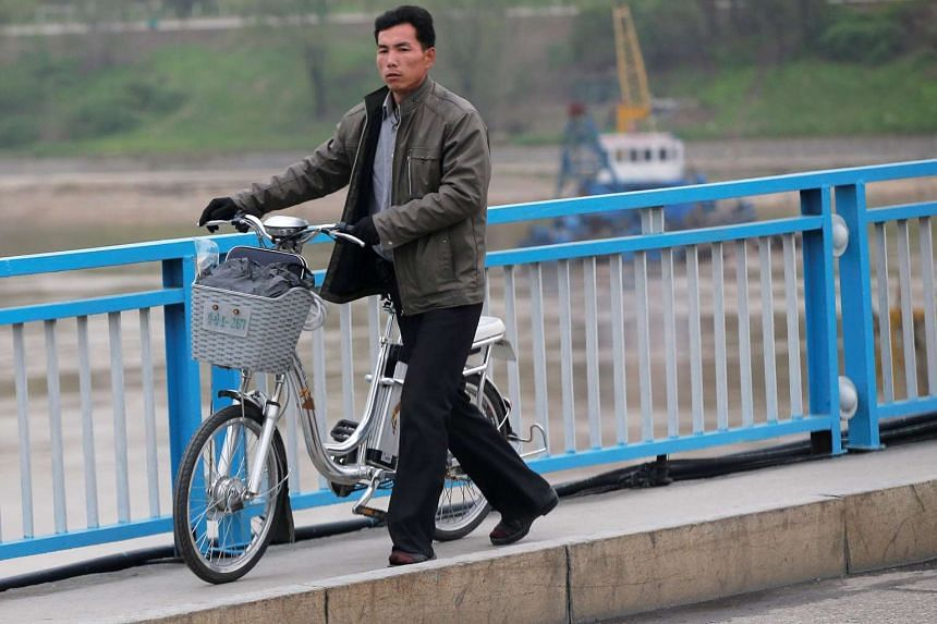 A man pushes an electric bicycle over a bridge in Pyongyang, North Korea, on May 6, 2016.