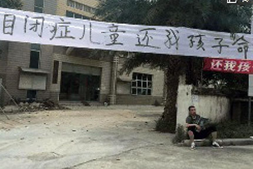 """Jia Jia's father (left) sitting under a banner that reads """"I want my son back"""" outside the rehabilitation centre in Guangdong. The little boy (above) was autistic."""