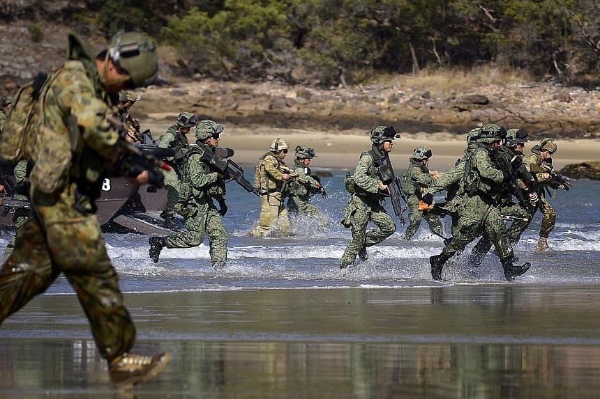 Soldiers from the SAF Guards battalion and the Australian Defence Force's 7th Australian Regiment carrying out a beach landing in the Shoalwater Bay Training Area in 2014, during a preview of Exercise Trident.