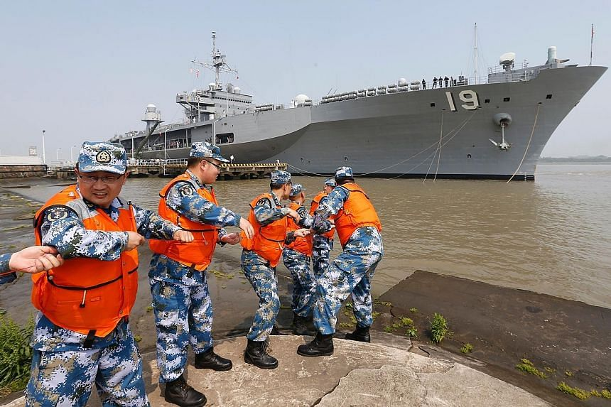 Chinese military personnel hauling in a rope as the USS Blue Ridge berthed in Shanghai yesterday. The visit of the command ship of the US Seventh Fleet comes just days after China denied a port call for a US aircraft carrier in its special administra