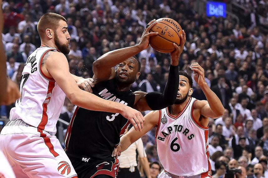 Miami Heat guard Dwyane Wade (centre) being sandwiched by Toronto Raptors centre Jonas Valanciunas (left) and guard Cory Joseph in their NBA play-offs Game 2 clash. Their Eastern Conference semi-final series is tied at 1-1.