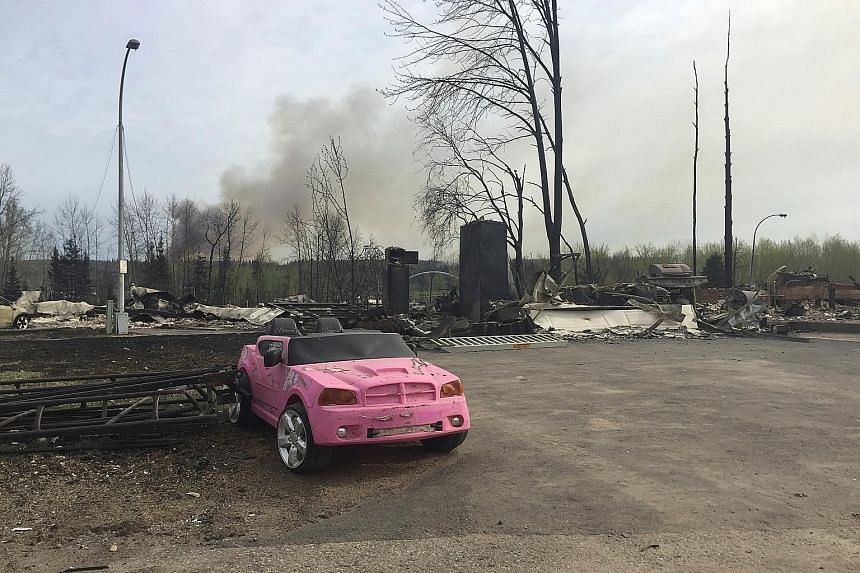 (Clockwise from right) A pink car sits forlorn among the ruins after wildfires tore through Fort McMurray this week; a wasteland of destroyed homes; evacuees taking stock of their situation.
