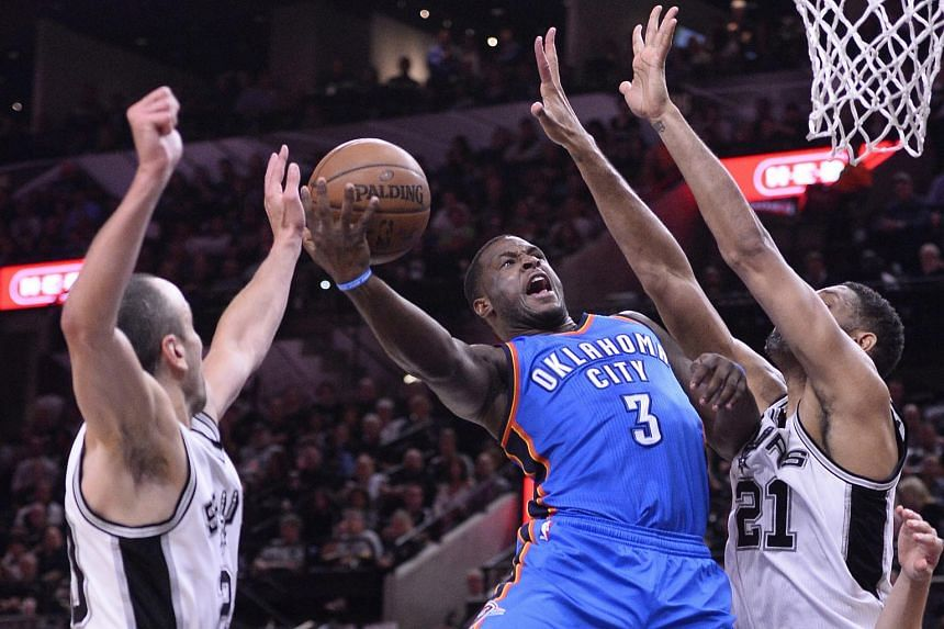 Oklahoma City Thunder guard Dion Waiters (centre) playing against San Antonio Spurs' Tim Duncan (right) and Manu Ginobili (left) on May 2.