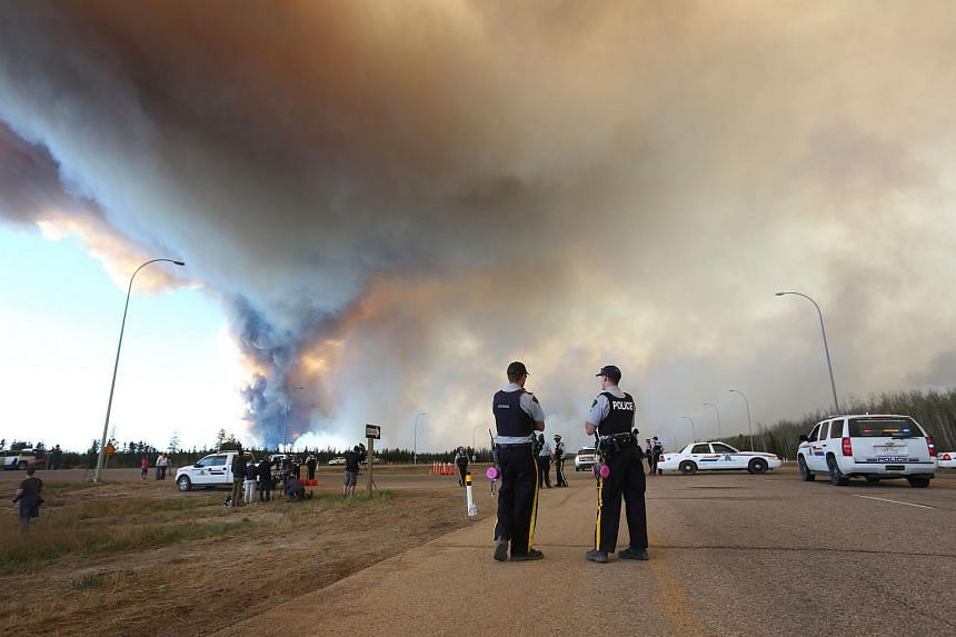 Police officers working around a road block as smoke rises from a forest fire along the highway near Fort McMurray on May 6.