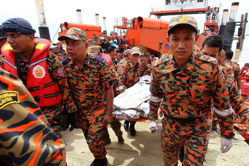 Members of the Sarawak Fire and Rescue Department carrying the body of a victim on May 6.