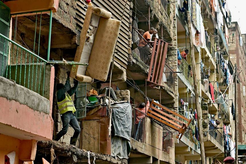 Residents move sofas and beds from a block of flats which is going which is going to be demolished on May 6, 2016.