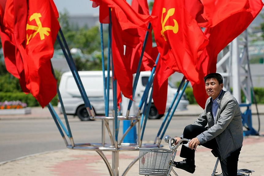 A man waiting to cross the street in front of Workers' Party of Korea (WPK) flags decorating an intersection in central Pyongyang, North Korea, on May 7, 2016.