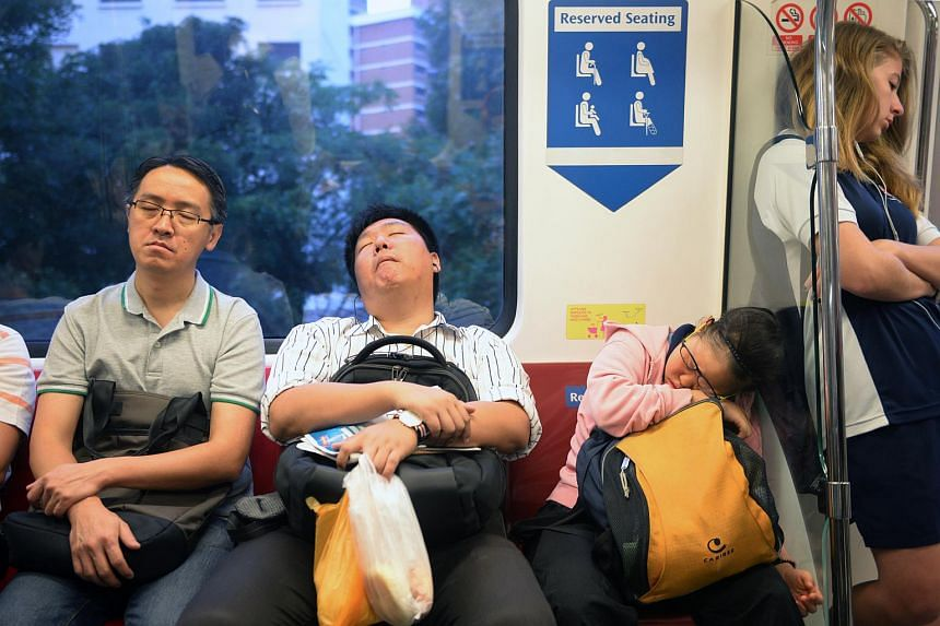 Early morning commuters catching some sleep on the MRT in Singapore.
