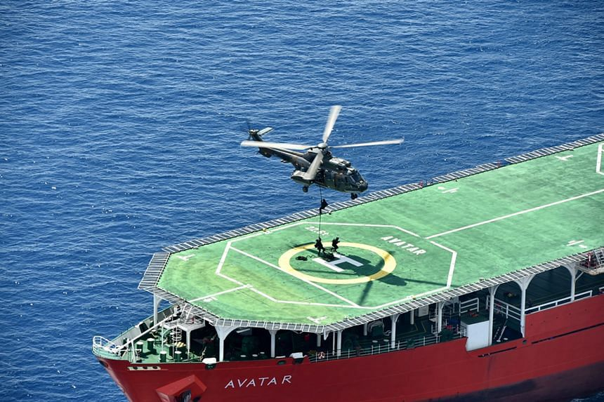 The Singapore Armed Forces Special Forces team fast-roping onto the deck of MV Avatar as the other multinational Special Forces teams storm the ship via rigid-hull inflatable boats.