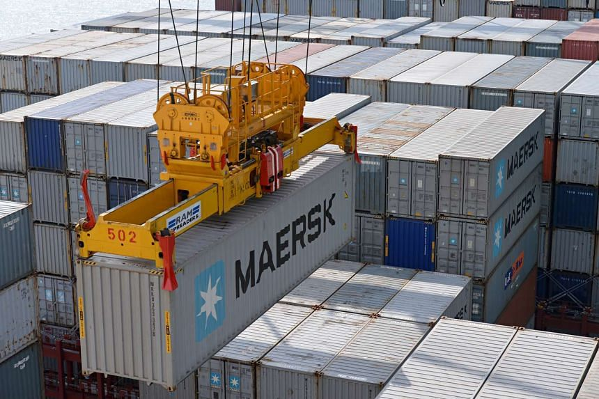 A MAERSK container being moved at a port in Singapore.