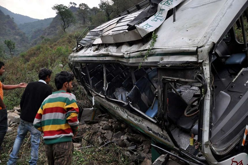 People look at the mangled remains of the bus on the spot where it fell into a gorge, at Golu near Jogindernagar, Himachal Pradesh, India on May 8, 2016.