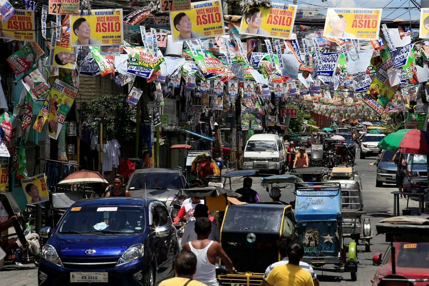 Election posters of Philippine candidates are seen hanging above vehicles driving along a main street in Tondo city, metro Manila on May 8, 2016.