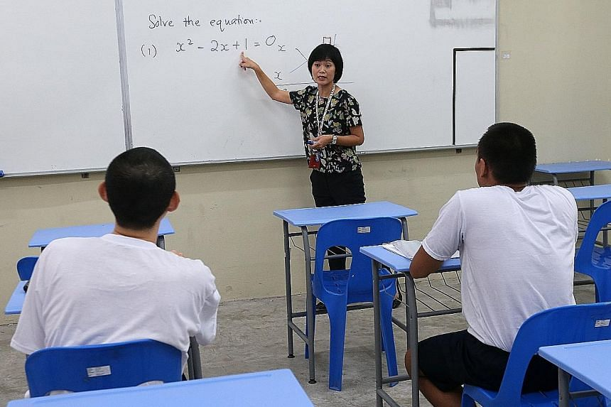 Above: Student inmates Paul (left) and Rahim (not their real names) in a prison school classroom with the school's vice-principal, Ms Phang Ka Leng. Top: The inmates reading in the library.