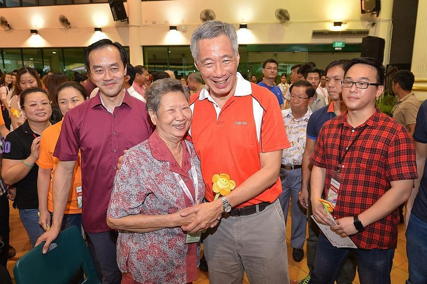 Yio Chu Kang resident Khoo Siang Heng, 78, receiving a flower from Prime Minister Lee Hsien Loong yesterday at a Mother's Day celebration. Beside them is Dr Koh Poh Koon, Minister of State for National Development and Trade and Industry. About 2,000