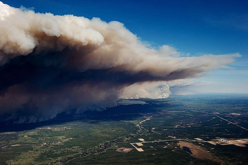 Huge plumes of smoke rising from the fire near Fort McMurray. More than 80,000 people have fled as the flames razed entire neighbourhoods.