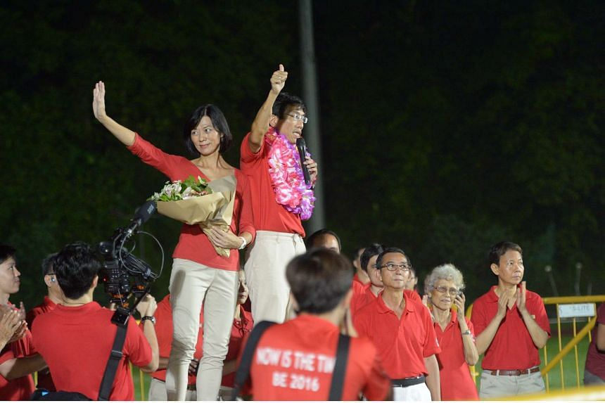 SDP's Chee Soon Juan, accompanied on stage by his wife, waving to supporters at Bukit Gombak Stadium.