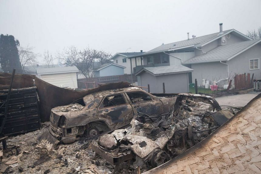 The remains of charred vehicles in a heavily damaged residential neighbourhood in Fort McMurray, Alberta.