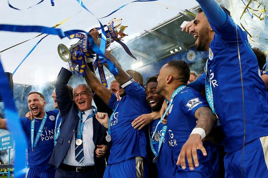 Leicester City's Wes Morgan and manager Claudio Ranieri lift the trophy as they celebrate winning the Barclays Premier League.