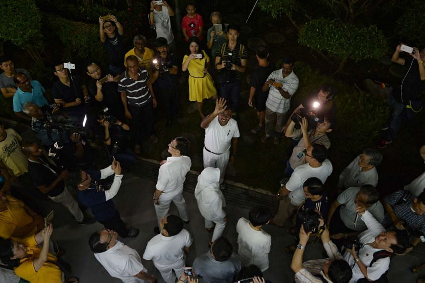 PAP's Murali Pillai, surrounded by supporters, waving at a camera above him before the announcement of the Bukit Batok by-election result.