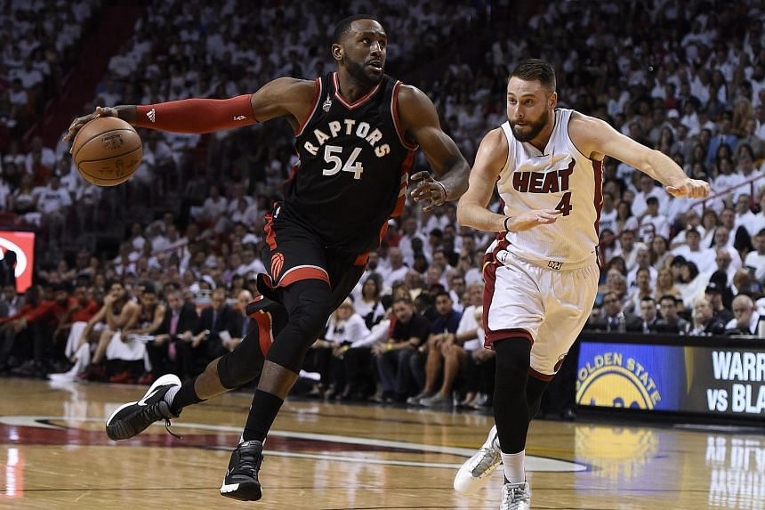 Toronto Raptors forward Patrick Patterson (left) drives the ball past Miami Heat forward Josh McRoberts.
