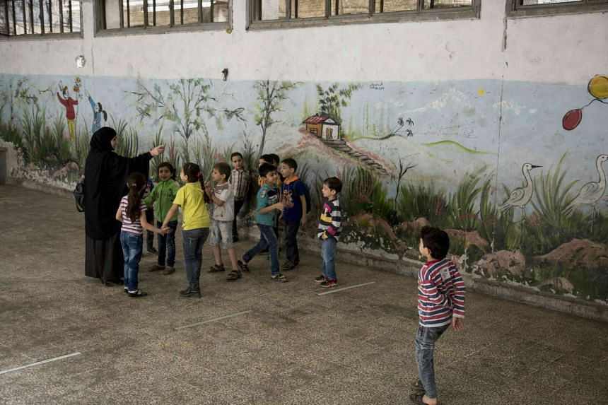Syrian children stand in the courtyard of their school in Aleppo's rebel-held eastern district of Shaar on May 7, 2016.