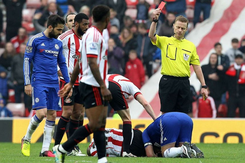 Referee Mike Jones shows a red card to Terry (right) following his challenge on Sunderland midfielder Wahbi Khazri.