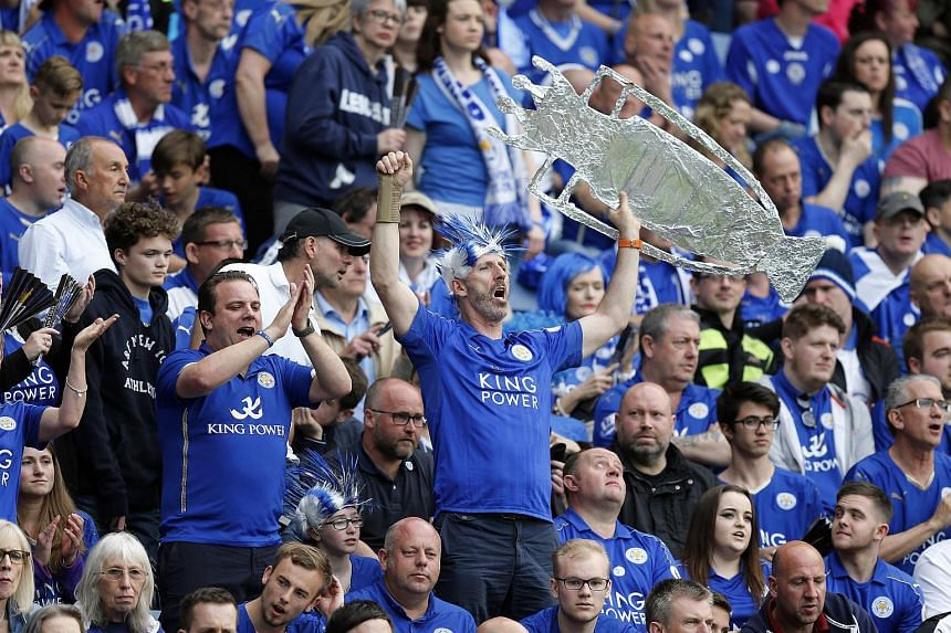 A Leicester City fan with a cut out trophy celebrates winning the Barclays Premier League.