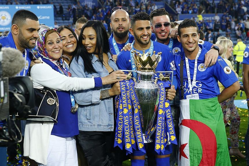 Leicester City's Riyad Mahrez holds the trophy as he celebrates winning the Premier League with his family.