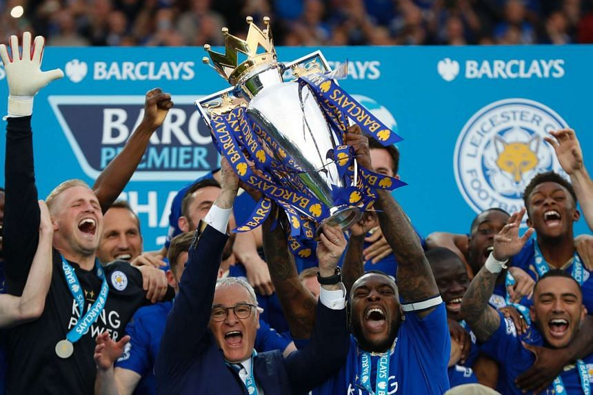 Leicester City's Italian manager Claudio Ranieri (centre) and Leicester City's English defender Wes Morgan hold up the Premier league trophy.