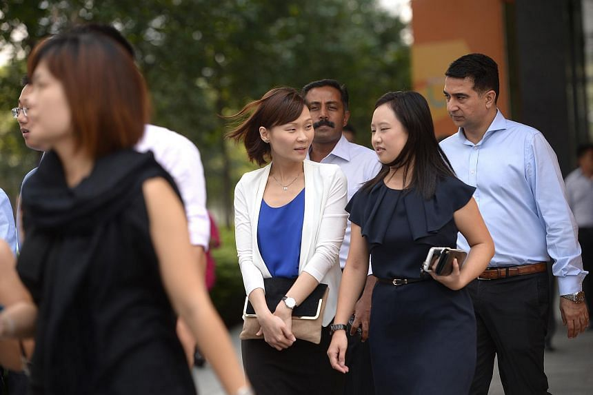 Office workers having a conversation at Marina Bay Financial Centre on Sept 2, 2014.