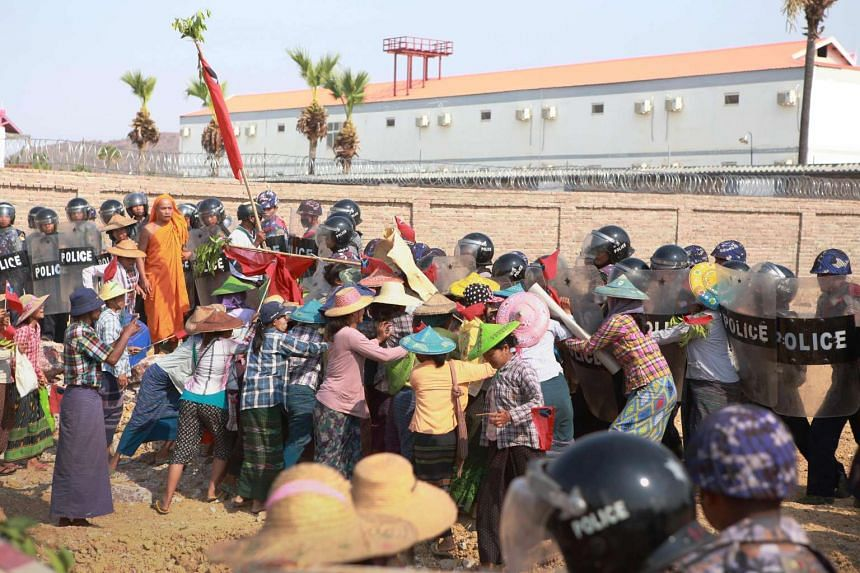 Demonstrators face Myanmar policemen during a protest outside the Chinese owned mining facility in the central town of Monywa, on May 6, 2016.