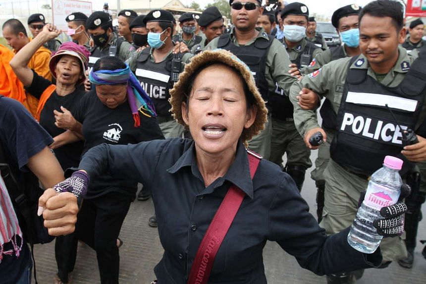 Cambodian police officers block Human Rights activists during a protest near Prey Sar prison, on the outskirts of Phnom Penh, on May 9, 2016.