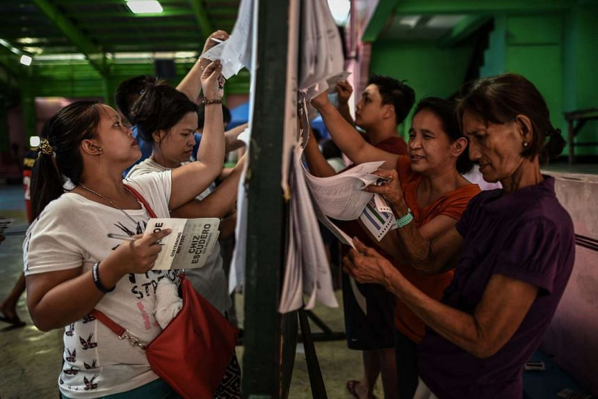 Filipino voters check for their names on lists before casting their votes in the country's presidential election at a polling centre in Manila.