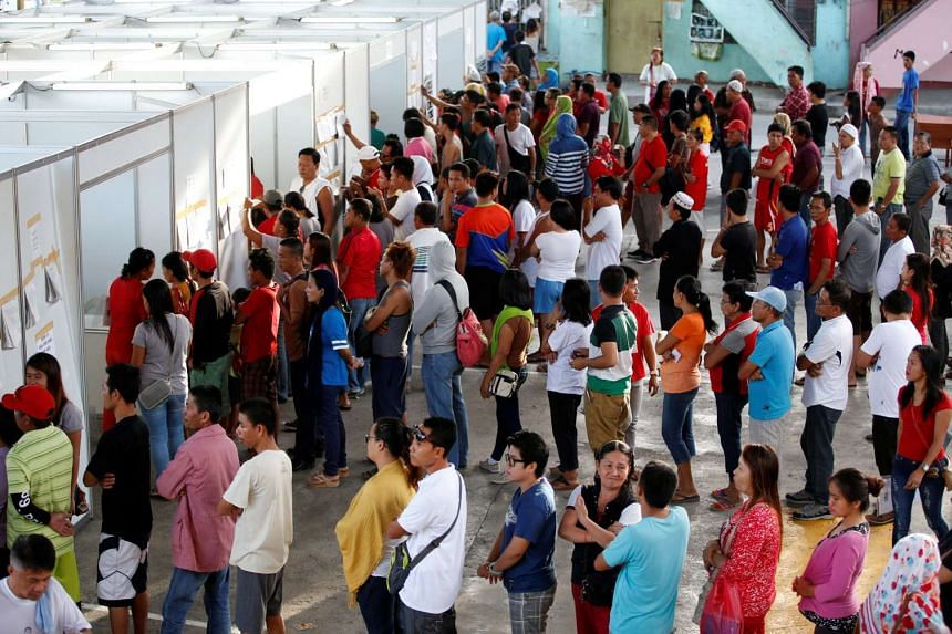Residents queue as they wait for his turn to vote during the national elections in Davao city in southern Philippines.