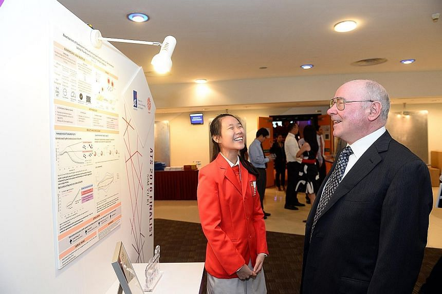 Yu Ki discussing her research project, a portable dengue fever diagnostic kit, with Professor Johann Deisenhofer, Nobel laureate and chief judge of the A*Star Talent Search Awards Committee.